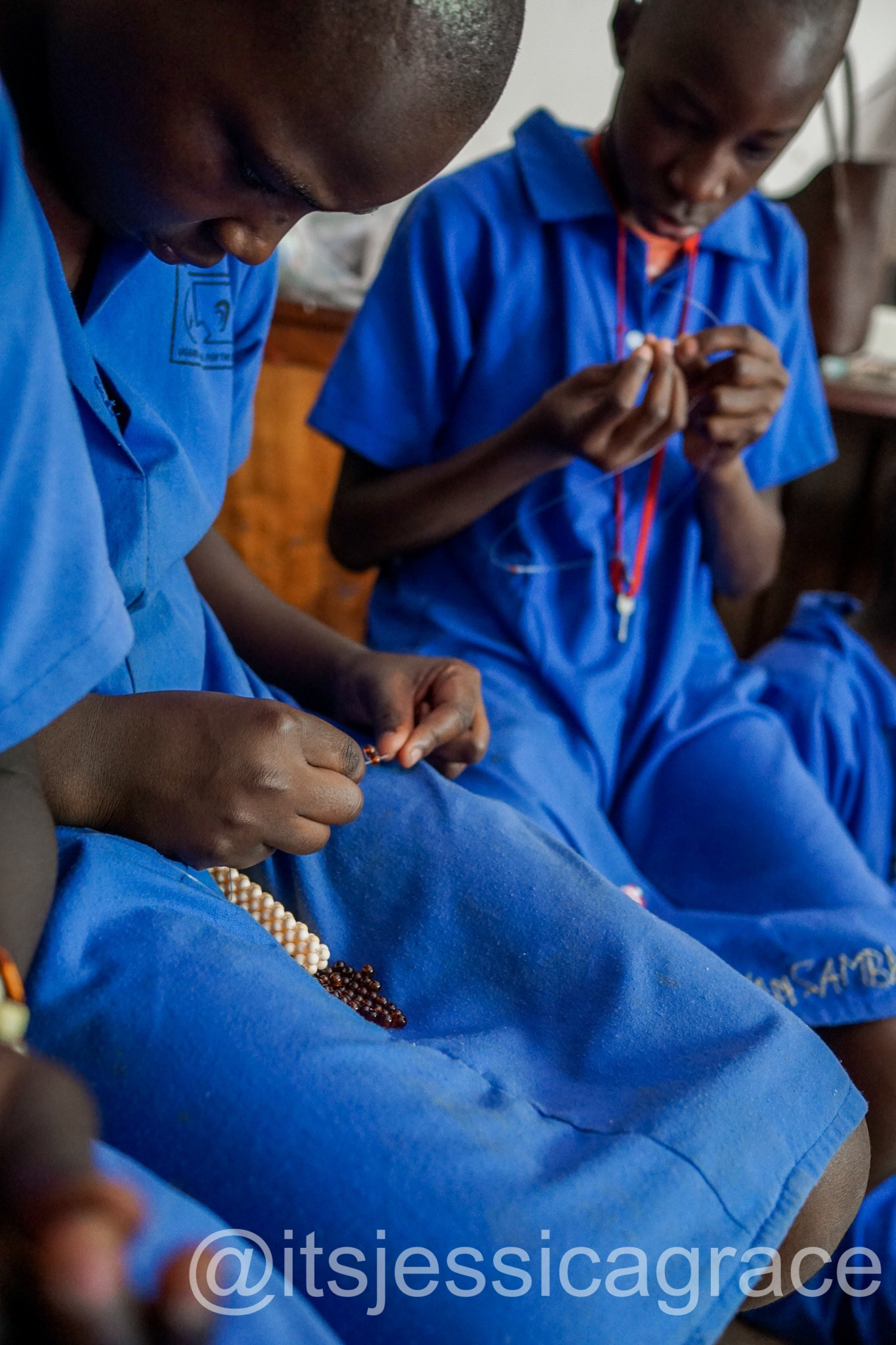 girls threading beads at the Uganda School for the Deaf